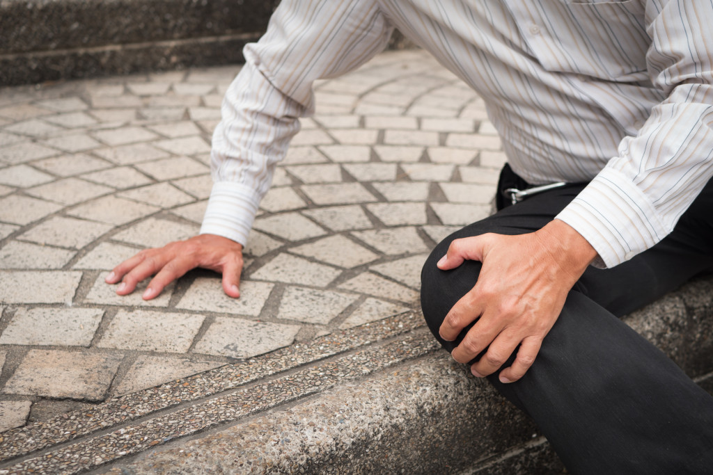 man hurt knee in pavement